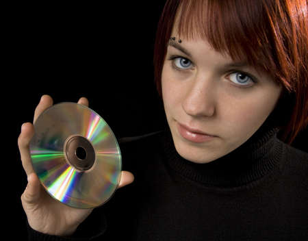 Girl holding a compact disc and looking in the camera, beautiful. Her reflection mirrored on the disc surface. Stock Photo - 2290416