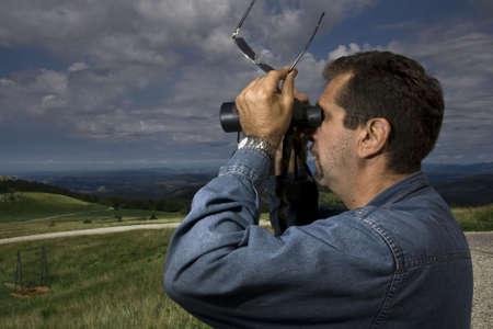 scouting: Man using his binoculars on a hiking trip scouting while traveling