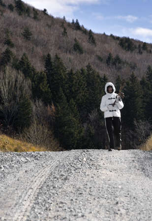 white coat: Woman in a white coat walking down a country road towards the camera. Holding dry flowers. Stock Photo