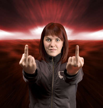 middle finger: Redhead girl showing middle fingers with a dramatic apocalyptic background. Stock Photo