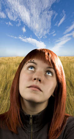 Girl filled with hope and optimism staring at the blue sky. photo