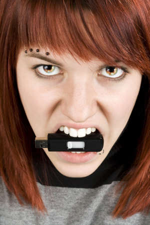 animosity: Beautiful redhead girl biting an usb memory stick with eyes on fire. Concept alluding to hate against computers or computer equipment.Studio shot. Stock Photo