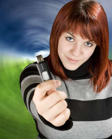 Beautiful redhead girl holding an usb memory stick or flash drive at the camera.Studio shot. Zdjęcie Seryjne