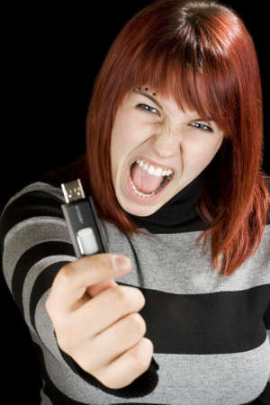 grimace: Beautiful redhead girl holding an usb memory stick or flash drive at the camera with an angry expression.Studio shot.