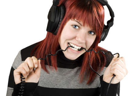 sound bite: Cute girl with red hair biting the cord of her headphones while listening to music.Studio shot.