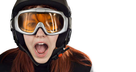 Cute girl with red hair wearing a ski helmet and orange goggles acting surprised and yelling. Feeling cold.Studio shot. photo
