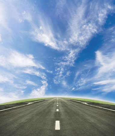 Shot of a tarmac road leading into the horizon. Beautiful blue sky and green slope beneath it. photo