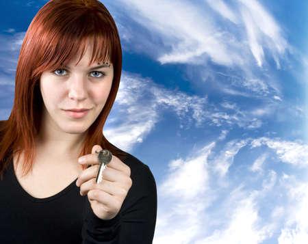 homebuyer: Cute redhead girl giving key for a new home.Studio shot.