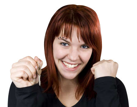 homebuyer: Studio shot of a cute redhead girl holding home or car keys and smiling her success out.