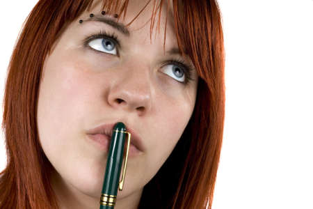 redhair: Cute girl with redhair pensive with pen on her lips.