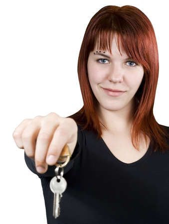 homebuyer: Cute smiling redhead girl holding keys towards the camera.
