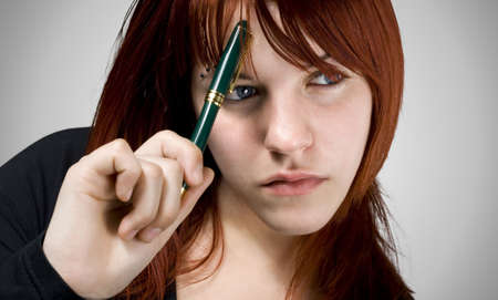 Cute girl with red hair holding a pen against her forehead and thinking.Studio shot. Stock Photo - 2297066
