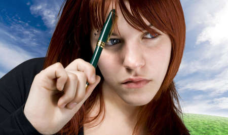 Cute girl with red hair holding a pen against her forehead and thinking.Studio shot. Stock Photo - 2297072
