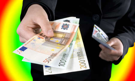 Hand giving Euro banknotes of 50, 100 and 200 Euro with another hand in the background keeping the spare. Colorful casino background.Studio shot. Stock Photo - 2297054