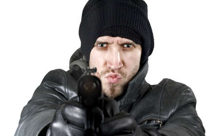 delinquent: Portrait of an undercover agent or delinquent dressed in black leather and balaclava hat firing handgun in the camera.Studio shot.