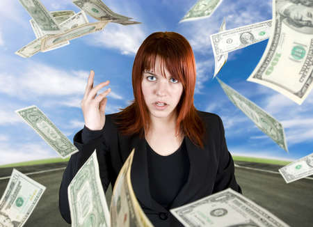 Angry and pretty redhead girl throwing Dollar banknote money towards the camera. Stock Photo - 2319891