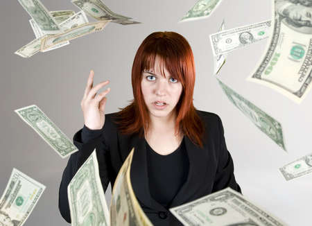 corporate waste: Angry and pretty redhead girl throwing Dollar banknote money towards the camera.