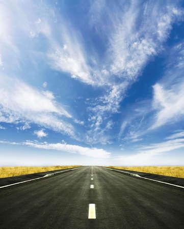 jasny: Piękny strzał z niebieskiej wysokości pochmurne niebo i żywe żółty wysokiej trawy. Centralny drogi prowadzącej do linii horyzontu. Zdjęcie Seryjne