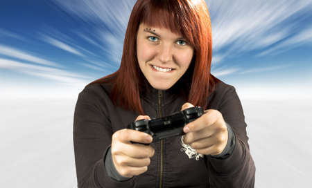 Photo of a happy beautiful redhead girl biting lips while playing video games. photo