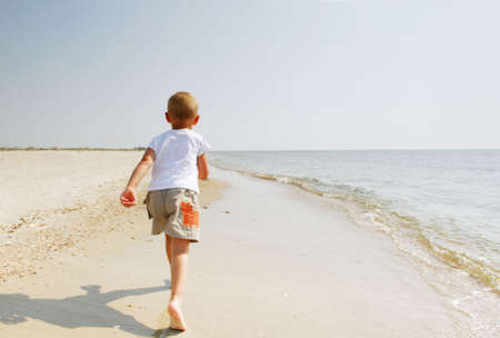 Young boy running along beach by sea, seen from behind. photo