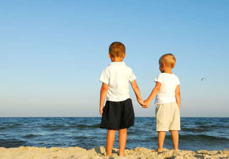 Back view of two caucasian boys holding hands and watching the sea