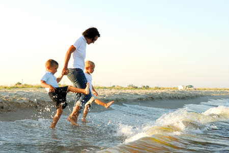 wade: Partial profile of a woman holding the hands of two young boys, as they splash their feet in shallow water ahead of oncoming waves. Stock Photo