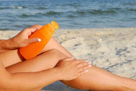 suntanning: Woman applying lotion to leg on sandy beach by water.