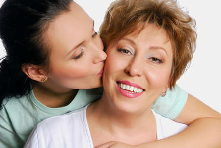 Yuong adult daughter kissing her senior mother photo