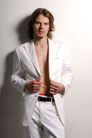 man with a goatee: Beauty adult male in the white suit posing in studio Stock Photo