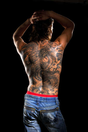 dragon vertical: Male back with tattoo. Stock Photo