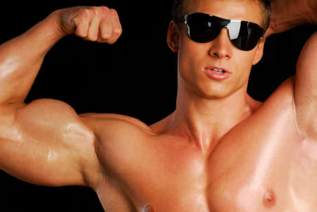 Portrait of strong man in the black sunglasses. Isolated on black. Stock Photo - 3714757
