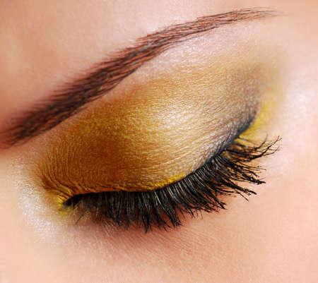 Moda maquillaje sombra de ojos de color amarillo brillante en los ojos cerrados