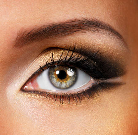 eyeshadows: Beautiful shape of female eye with golden-brown cosmetic make-up
