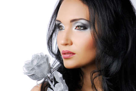 Attractive woman with silver rose at face  photo