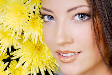 Close-up attractive female face with yellow camomile photo