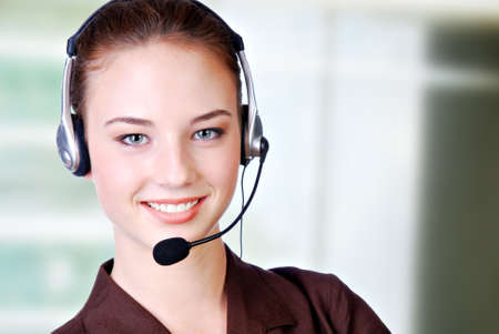 hands free phone: Close-up de la cara sonriente mujer en los auriculares en la oficina Foto de archivo