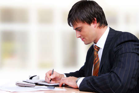 Attractive mature adult man sitting from the table and working Stock Photo