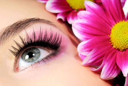 Close-up of woman green eye. Pink flower on background. photo