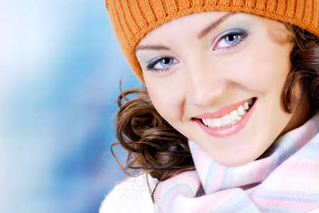 expressing: Happy young woman face with beauty smile dressed in the winter hat, scarf. People winter concept. Stock Photo