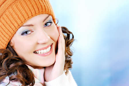 winter fashion: Cheerful woman face clothing in warm orange hat. Winter season.