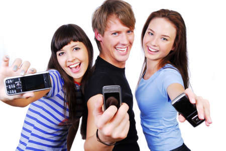 Two young woman and a man between them. Theyre showing mobile phones screen. Isolated on white in studio. photo