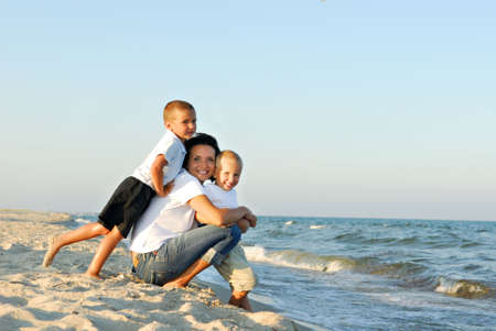 lean back: Young woman with two boys on the sand by the ocean.