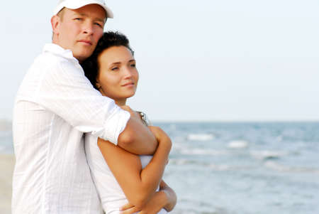 Portrait of happy couple embracing by sea. Stock Photo