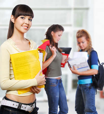 foreground: Clever student holding yellow folder in hands - focus on foreground. În background standing  classmates.