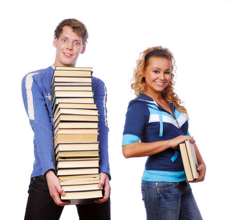 Two funny students holding the heap of books
