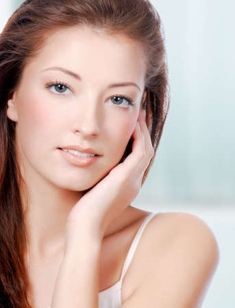 touching: Natural health beauty  of a woman face - colored background
