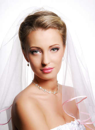 Portrait of cute young bride wearing the white vial. Fashion wedding shot on a white photo