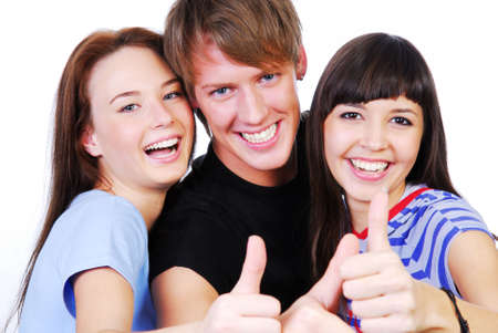 Portrait of a three young teenagers laughing and giving the thumbs-up sign. photo