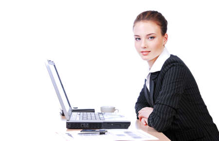 Attractive businesswoman sitting at table and working on a laptop photo