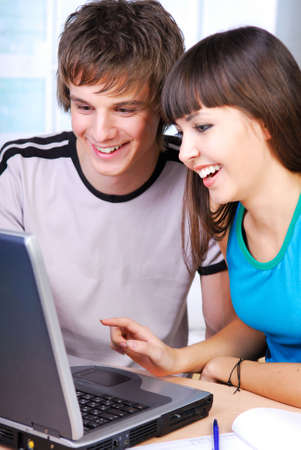 Two cheerful student sitting from the laptop and working photo